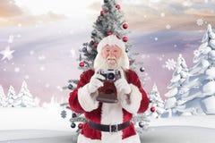 Санта Клаус держа камеру против цифров произведенной предпосылки Стоковые Изображения RF