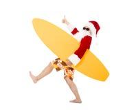 Санта Клаус держа доску прибоя с большим пальцем руки вверх Стоковая Фотография