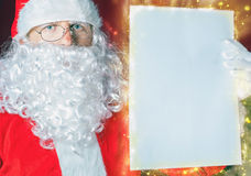 Санта Клаус держа wishlist, белое письмо или бумагу Стоковое Изображение RF