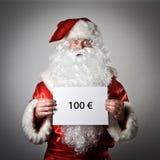Санта Клаус держит белую бумагу в его руках 100 e Стоковое Фото