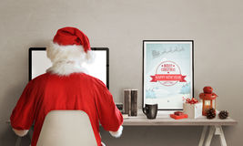 Санта Клаус занимается серфингом сеть на компьтер-книжке На его таблице фонарик, изображение, подарки, книги и чашка горячего чая Стоковые Изображения