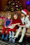 Санта Клаус и группа в составе девушки читая книгу Стоковое Изображение RF