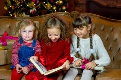 Санта Клаус и группа в составе девушки читая книгу Стоковая Фотография RF