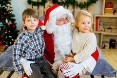 Санта Клаус и 2 дет сидя на кровати Стоковое фото RF