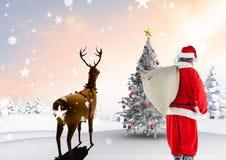 Санта Клаус идя на снежный ландшафт с северным оленем Стоковая Фотография RF