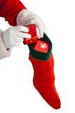 Санта Клаус кладя настоящие моменты в чулки рождества стоковые фотографии rf