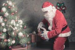 Санта Клаус кладя подарочную коробку или настоящий момент под рождественскую елку Стоковая Фотография RF