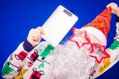 Санта Клаус на голубой предпосылке держа ПК таблетки Стоковые Фотографии RF