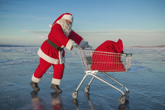 Санта Клаус носит магазинную тележкау с подарками в мешке Стоковая Фотография RF