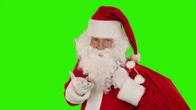 Санта Клаус нося его сумку, взгляды на камере, посылает поцелуй и волну, зеленый экран, отснятый видеоматериал запаса акции видеоматериалы
