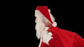 Санта Клаус нося его сумку, взгляды на камеру и winks, черноту, отснятый видеоматериал запаса видеоматериал