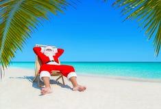 Санта Клаус ослабляет в sunlounger на песочном тропическом Palm Beach стоковые изображения