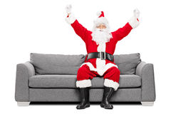 Санта Клаус показывать счастье усаженное на софу Стоковое Изображение