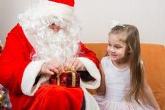 Санта Клаус помогает развязать подарку ленты, маленькой девочке счастливо смотря его Стоковое Фото