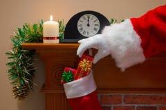 Санта Клаус поставляя настоящие моменты на Рожденственской ночи Стоковые Изображения