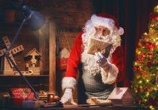 Санта Клаус подготавливает подарки Стоковые Изображения RF