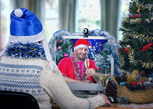 Санта Клаус при хелпер наслаждаясь рождеством онлайн Стоковое Фото