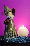 Санта Клаус развевая его рука и свеча горения на magenta предпосылке Стоковая Фотография