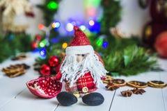Санта Клаус сидя на белом деревянном столе на предпосылке зеленых гирлянд и светов рождества Стоковая Фотография