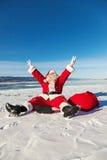 Санта Клаус сидя на новостях снега радостных в компьтер-книжке Стоковое Изображение