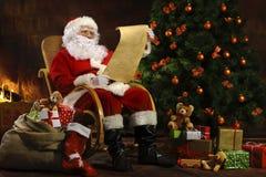 Санта Клаус сидя перед камином Стоковые Изображения RF
