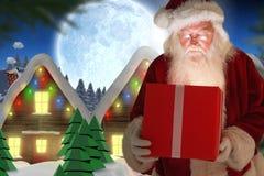 Санта Клаус смотря подарок рождества Стоковые Фото