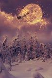 Санта Клаус с летанием северного оленя через небо Стоковая Фотография RF