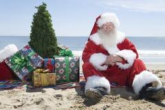 Санта Клаус с настоящими моментами и дерево сидя на пляже стоковая фотография rf