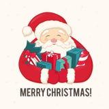 Санта Клаус с рождественской елкой и подарками в руках Стоковые Изображения