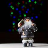 Санта Клаус с сумкой настоящих моментов на черной предпосылке стоковые фото