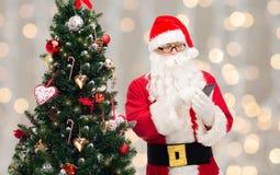 Санта Клаус с smartphone и рождественской елкой Стоковое Изображение