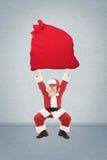 Санта Клаус тренирует для того чтобы поднять очень тяжелую сумку с подарками Стоковая Фотография