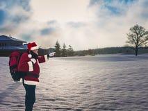 Санта при большой красный рюкзак стоя в зиме покрытой снег стоковая фотография