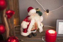 Санта стоит на полке с гирляндами и свечами Стоковые Изображения
