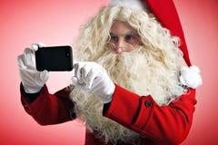 Санта с устройствами в руках Стоковая Фотография RF