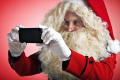 Санта с устройствами в руках Стоковое Изображение