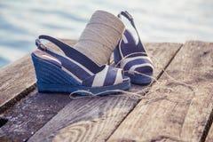 Сандалии джинсовой ткани голубые лежат на деревянной муфте на озере Стоковая Фотография RF