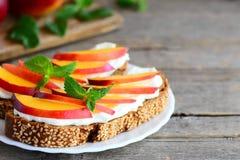 Сандвичи здравицы нектарина и плавленого сыра Открытые сандвичи сделанные из хлеба рож с плавленым сыром и свежими кусками нектар Стоковые Изображения