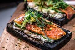Сандвичи копченых семг хлеба угля на деревянной доске Стоковые Фото