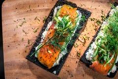 Сандвичи копченых семг хлеба угля на деревянной доске Стоковое фото RF
