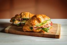 Сандвичи круассанов на деревянной разделочной доске Стоковое Изображение