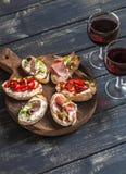 Сандвичи с козий сыром, камсы, зажарили в духовке перцы, ветчину и 2 стекла красного вина на деревянной деревенской доске стоковая фотография