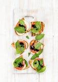 Сандвичи Caprese с томатом, сыром моццареллы, базиликом и бальзамической поливой на белизне покрасили деревянную предпосылку Стоковая Фотография