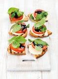 Сандвичи Caprese с томатом, сыром моццареллы, базиликом и бальзамической поливой на белизне покрасили доску над светлое деревянны Стоковое фото RF