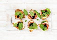 Сандвичи Caprese с томатом, сыром моццареллы, базиликом и бальзамической поливой на белизне покрасили деревянную предпосылку Стоковые Изображения