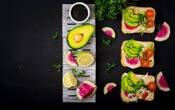 Сандвичи Vegan с авокадоом, редиской арбуза и томатами на черной предпосылке Стоковые Фото
