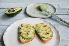 Сандвич авокадоа на белой handmade плите Стоковые Изображения RF