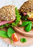 Сандвич бургера с ветчиной, сыром, томатами и салатом Стоковое Фото