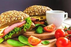 Сандвич бургера с ветчиной, сыром, томатами и салатом Стоковые Фото