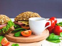 Сандвич бургера с ветчиной, сыром, томатами и салатом Стоковые Фотографии RF
